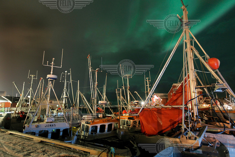 Northern lights, aurora borealis, over the island of Røst in Lofoten. Docked fishing boats in the foreground.