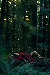 Young woman in red dress lying on a tree in a beautiful tranquill deep green mossy woods magical nature scenery Image © MaximImages, License at https://www.maximimages.com