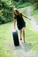 Young woman pushing tire