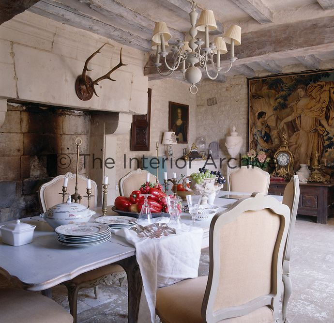 The dining room is dominated by a massive stone fireplace and a tapestry against the far wall
