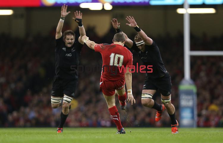 Wales outside half Dan Biggar kicks the ball away under pressure from All Blacks pair Richie McCaw and Kieran Read.<br /> Dove men Series 2014<br /> Wales v New Zealand<br /> 22.11.14<br /> ©Steve Pope -SPORTINGWALES