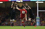 Wales outside half Dan Biggar kicks the ball away under pressure from All Blacks pair Richie McCaw and Kieran Read.<br /> Dove men Series 2014<br /> Wales v New Zealand<br /> 22.11.14<br /> ©Steve Pope -SPORTINGWALES