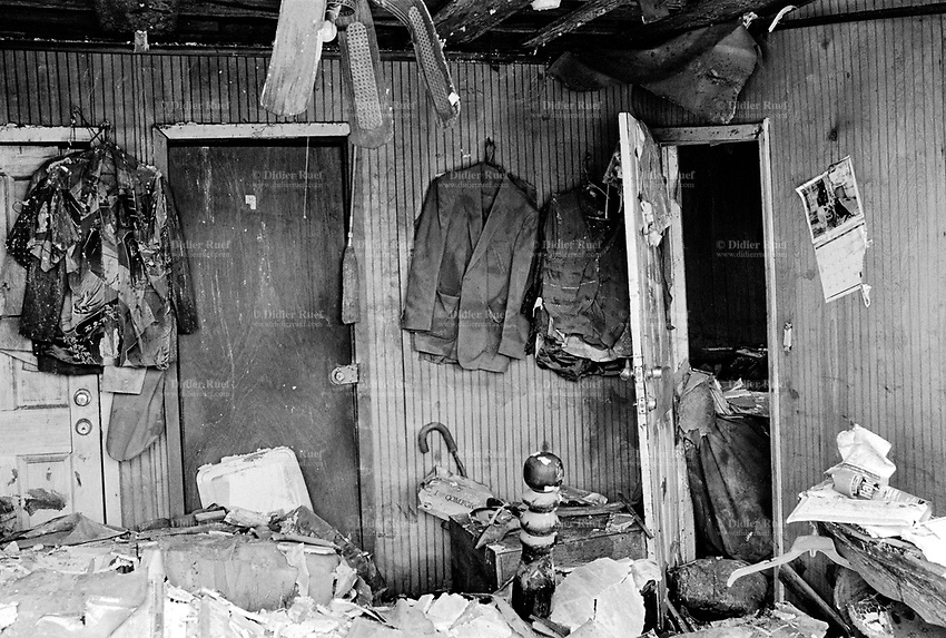 USA. Louisiana. New Orleans. Orleans Parish. 9th Ward area. The 9th Ward used to be the living place of the black (afro-american) community . Aftermath of hurricane Katrina. The interior of a poor house (clothes, fan, bed, shelves, door, furniture) destroyed by the floods, like all houses of the area.The area is empty and all its inhabitants have left the town. The people could no longer and ever live again in the houses because of the destructions due to the floods, the  water and the mold. The entire area needs to be bulldozed before any new construction can be built.  Household waste. © 2005 Didier Ruef