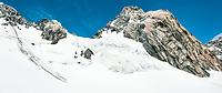 Mount Spencer 2788m of Southern Alps above Franz Josef Glacier. Group of tiny climbers under mountain near saddle, Westland Tai Poutini National Park, UNESCO World Heritage Area, West Coast, New Zealand, NZ