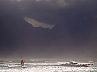 Sun rays beam through ocean spray and mist on a windsurfer at Ho'okipa Beach Park, with mountains touched by clouds in the distance, Maui.