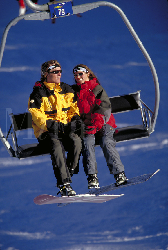 Woman, Man, Scenic, Active Lifestyle, Winter, Snowboarding, Sports, Exercise, Training, Fitness, Friends, Couples, Love, Dating, Fun, Vacation. Young Couple (MR 657, 641) On Chairlift. Colorado United States Rocky Mountains, Summit County, Copper Mountain