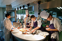 Chef Mauro Colagreco (left) plates dishes with his staff in the kitchen of restaurant Mirazur, Menton, France, 18 September 2013