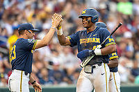 Michigan Wolverines designated hitter Jordan Nwogu (42) is greeted by head coach Erik Bakich (23) after scoring during Game 6 of the NCAA College World Series against the Florida State Seminoles on June 17, 2019 at TD Ameritrade Park in Omaha, Nebraska. Michigan defeated Florida State 2-0. (Andrew Woolley/Four Seam Images)