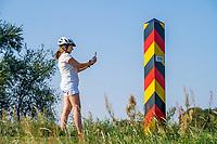 Frau fotografiert einen deutschen Grenzpfosten, Lebus, Oder-Neiße-Radweg, Märkisch Oderland, Brandenburg, Deutschland