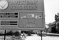 """Russia. Krasnodar Krai Region. Krasnodar. People walk on the street in the city center. Billboard with an advertising for """" Investbank Krasnodar"""". Banknotes drawings: 100 dollars, 500 Soviet rubles, and100 Deutsche Mark. The United States one-hundred-dollar bill ($100) is a denomination of United States currency. The first United States Note with this value was issued in 1862 and the Federal Reserve Note version was launched in 1914, alongside other denominations. Statesman, inventor, diplomat, and American founding father Benjamin Franklin has been featured on the obverse of the bill since 1914.The $100 bill is the largest denomination that has been printed and circulated since July 13, 1969. The Soviet ruble was the currency of the Russian Soviet Federative Socialist Republic from 1917 and later the Union of Soviet Socialist Republics (USSR). In 1991, after the breakup of the USSR, the Soviet ruble continued to be used in the post-Soviet states, forming a """"ruble zone"""", until it was replaced with the Russian ruble in September 1993. The Deutsche Mark was the official currency of West Germany from 1948 until 1990 and later the unified Germany from 1990 until 2002. It served as the Federal Republic of Germany's official currency from its founding the following year until the adoption of the euro. In English it is commonly called the """"Deutschmark"""". Krasnodar (also known as Kuban) is the largest city and the administrative centre of Krasnodar Krai in Southern Russia. 18.9.1993 © 1993 Didier Ruef"""