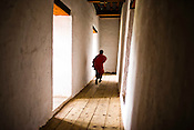 A Buddhist monk runs through the corridors to attend the prayers inside the Punakha Dzong (fortress) in Punakha, Bhutan. Phunakha was the capital of Bhutan and the seat of government until 1955, when the capital was moved to Thimphu. Punakha is the administrative centre of Punakha dzongkhag, one of the 20 districts of Bhutan. Photo: Sanjit Das/Panos