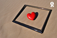 Heartshape into picture frame on sand  (Licence this image exclusively with Getty: http://www.gettyimages.com/detail/83154258 )