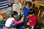 Preschool 4 year olds group of two boys and a girl playing together building structures from colorful plastic connecting bricks