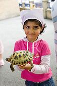 A girl holds with a tortoise at Church Street Summer Festival 2005, Paddington, London.