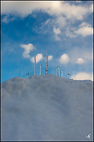 Upside-down icicles on snow in the aftnoon, with cartoonish clouds in the sky. The icicles resemble a strange icy cityscape of skyscrapers.