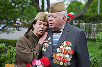 Moscow, Russia, 09/05/2011..A woman in Soviet-era army uniform sings on a veteran's shoulder as Russian World War Two veterans and well-wishers gather in Gorky Park during the country's annual Victory Day celebrations.