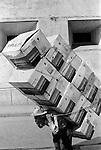 Managua Guatemala Central America. 1973. Man carrying eleven boxes of Remington Standard Typewriter boxes.