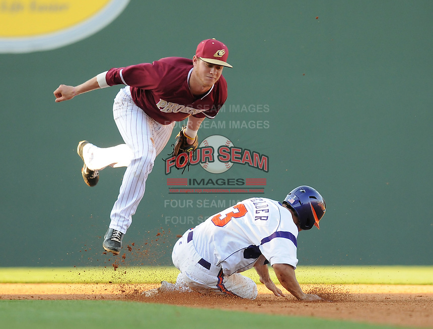Outfielder Brad Felder (3) of the Clemson Tigers steals second base as shortstop Chris Bresnahan (2) of the Elon College Phoenix takes a tumble reaching for the ball on March 21, 2012, at Fluor Field at the West End in Greenville, South Carolina. Clemson won 4-2, giving head coach Jack Leggett his 1,200th win. (Tom Priddy/Four Seam Images)