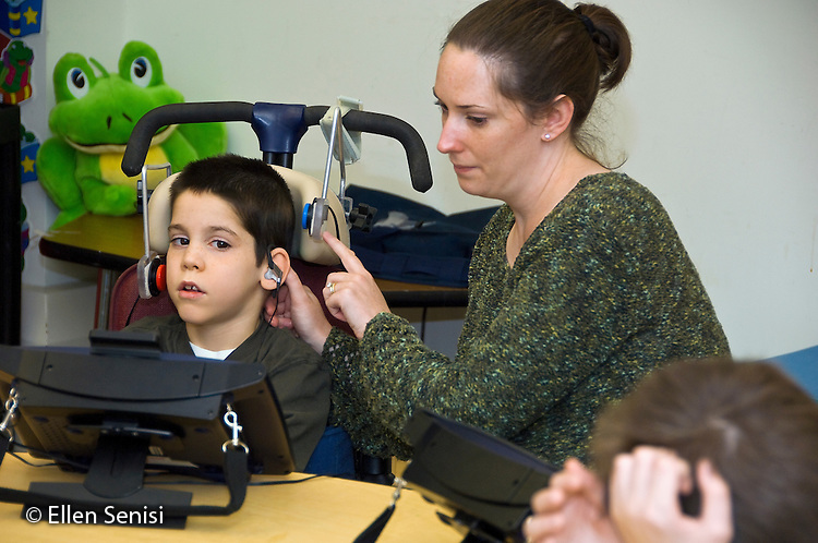 MR / Albany, NY.Langan School at Center for Disability Services .Ungraded private school which serves individuals with multiple disabilities.Speech language pathologist works with student during speech and language lesson. She is tapping the headphones to prompt him to access his augmentative and alternative communication device. Boy: 8, cerebral palsy, spastic quadriplegic, nonverbal with expressive and receptive language delays.MR: Hac2, Dub1.© Ellen B. Senisi
