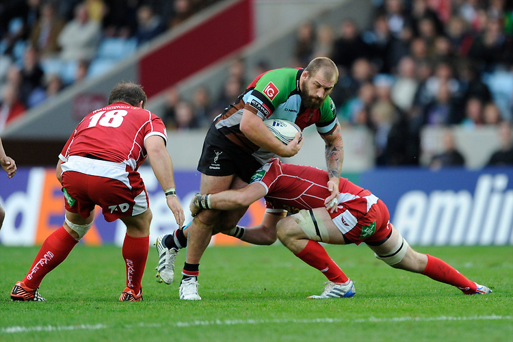 Joe Marler of Harlequins is tackled during the Heineken Cup Round 1 match between Harlequins and Scarlets at the Twickenham Stoop on Saturday 12th October 2013 (Photo by Rob Munro)