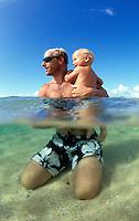 Hawaii, Kauai, Father & 13 m.o. baby girl in ocean, split level view.