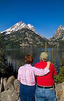 Retired senior couple relaxing at lake and enjoying the beautiful Grand Tetons mountain view, Jackson, Wyoming, National Park, USA