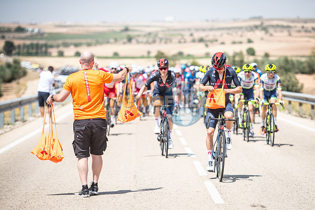 The peloton pass through the feedzone Stage 5 of La Vuelta d'Espana 2021, running 184.4km from Tarancón to Albacete, Spain. 18th August 2021.    <br /> Picture: Charly Lopez/Unipublic | Cyclefile<br /> <br /> All photos usage must carry mandatory copyright credit (© Cyclefile | Unipublic/Charly Lopez)