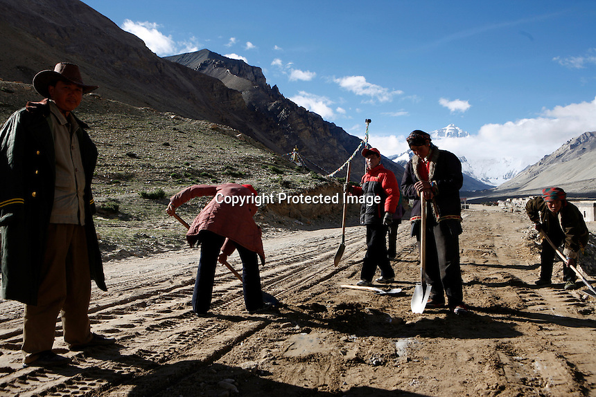 """China started building a controversial 67-mile """"paved highway fenced with undulating guardrails"""" to Mount Qomolangma, known in the west as Mount Everest, to help facilitate next year's Olympic Games torch relay./// Tibetans work with shovels and their bare hands building the road to Everest Base Camp.<br /> Tibet, China<br /> July, 2007"""