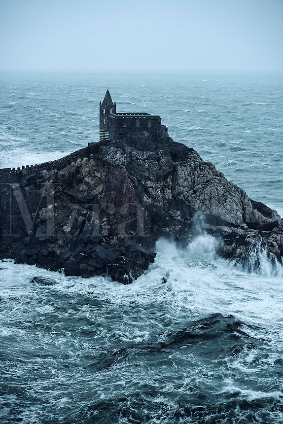 St Peters medieval church perched on a rocky precipice during coastal storm. Porto Venere, Italy