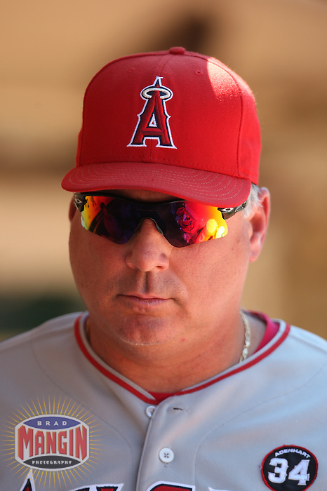 OAKLAND, CA - JULY 19:  Manager Mike Scioscia #14 of the Los Angeles Angels of Anaheim stands in the dugout against the Oakland Athletics during the game at the Oakland-Alameda County Coliseum on July 19, 2009 in Oakland, California. Photo by Brad Mangin