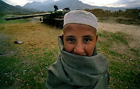 Salang Pass / Afghanistan.Un giovane afgano lungo la strada strategica del Passo del Salang che collega Kabul al nord dell'Afghanistan. Sullo sfondo i resti di un carro armato distrutto..Foto Livio Senigalliesi..Salang Pass / Afghanistan.Young boy selling fruits along the road of Salang Pass connecting Kabul with the north of Afghanistan.On the background one tank destroyed during the war..Photo Livio Senigalliesi