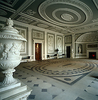 The stucco oval ceiling rose is mirrored in the pattern of the floor tiles of this grand entrance hall at Osterley Park designed by Robert Adam