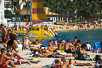 Waikiki beach with crowds on a hot day, with catamaran, island of Oahu