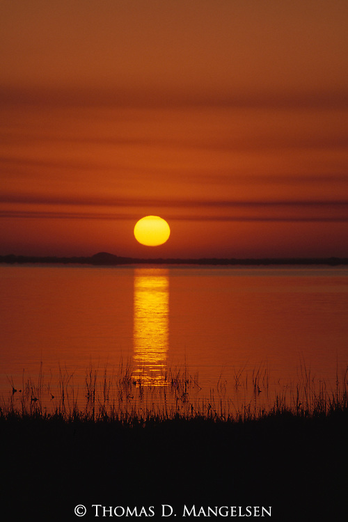 The setting sun reflects in a lake.