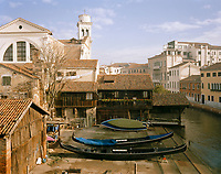 Moving away from the central tourist areas in Venice can reap rewards. Here, more modest housing looks over a dry dock, where a couple of gondolas are undergoing repairs.