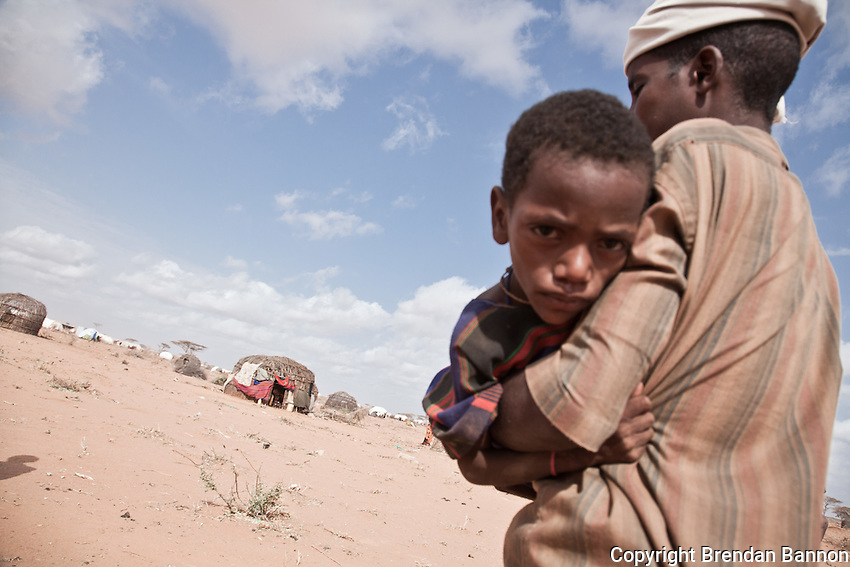 Somali refugee Ali Aden carries his four year old malnourished nephew to an emergency feeding center run by MSF atthe edge of Dagahaley settlement in Dadaab refugee camp.