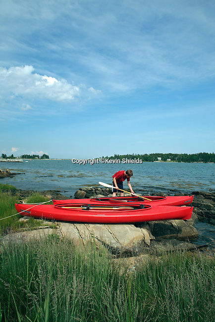 Young boy with kayaks at Spruce Head Island, South Thomaston, Maine, USA