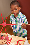 3 year old boy playing with wood stick and cube construction toy talking to himself vertical