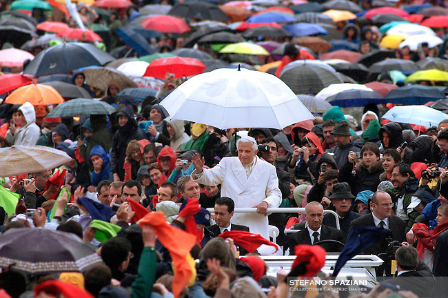 ope Benedict XVI is protected by the heavy rain as he acknowledges cheers from young pilgrims and faithful while touring St. Peter's square at the Vatican Saturday, March 24, 2007, during a meeting with young people of the Italian 'Comunione e Liberazione' organization.