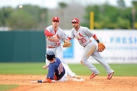 St. Louis Cardinals shortstop Pete Kozma #38 throws to first as Jake Elmore #10 slides in and Daniel Descalso #33 backs up the play during a Spring Training game against the Houston Astros at Osceola County Stadium on March 1, 2013 in Kissimmee, Florida.  The game ended in a tie at 8-8.  (Mike Janes/Four Seam Images)