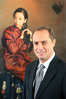 "Chairman of Treasury Holdings Richard Barrett poses for a photograph in front of Li Bin's ""Lady combing hair"" painting (2004) in Treasury Holdings headquarters in Shanghai, China, Tuesday, January 29, 2008. Photo by Lucas Schifres/Sinopix"