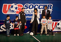 First Lady Michelle Obama passes a ball to the middle of a small pitch during a US Soccer Foundation clinic held at City Center in Washington, DC.