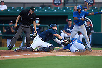 Lakeland Flying Tigers catcher Cooper Johnson (7) lunges to tag PK Morris (12) as umpire Kenny Jackson looks on to make the call during a game against the Dunedin Blue Jays on June 8, 2021 at Joker Marchant Stadium in Lakeland, Florida.  (Mike Janes/Four Seam Images)