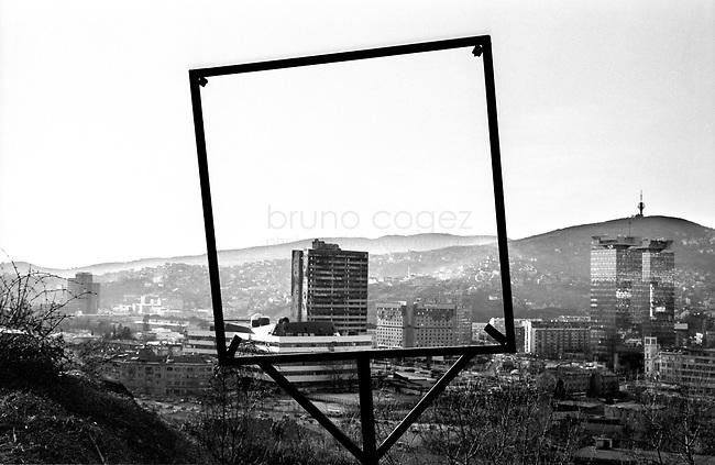 BOSNIA-HERZEGOVINA, Sarajevo, March 2003..10 years after the end of the war, I came for the first time in Sarajevo. I have in mind the images of the besieged city. The daily death, the impotence and the guilty inaction of the international community, the sad spectacle of a war in Europe. 10 years later, I walk the streets obsessed with the scars of war..View of the town from the hills on the burned parliament building..BOSNIE-HERZEGOVINE, Sarajevo, Mars 2003..10 ans après la fin de la guerre, j'arrive pour la première fois à Sarajevo. J'ai encore en tête les images de la ville assiégée. La mort quotidienne, l'impuissance voire l'inaction coupable de la communauté internationale, le spectacle désolant d'une guerre en Europe. 10 après, je déambule dans les rues obsédé par les stigmates de la guerre..Vue depuis les collines sur le batiment du parlement incendié pendant la guerre..© Bruno Cogez