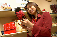 June 16 , 2002, Montreal, Quebec, Canada<br /> <br /> A Japanese tourist look at shoes in a Old Montreal shop, June 16 , 2002.<br /> <br /> Model released for all usages.<br /> <br /> Mandatory Credit: Photo by Pierre Roussel- Images Distribution. (©) Copyright 2002 by Pierre Roussel <br /> <br /> NOTE Nikon D-1 jpeg opened with Qimage icc profile, saved in Adobe 1998 RGB