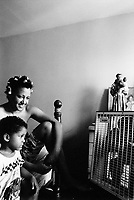 """USA. New York City. Spanish Harlem. Nina has put one's hair in rollers and seats on her bed with her younger son Papo. A religious statue is on the sideboard close to a photo and a fan. The Puerto Rican family lives below the poverty line and receives public assistance (AFDC, Home Relief, Supplemental Security Income and Medicaid). The family resides in units managed by the New York City Housing Authority (NYCHA) which provides housing for low income residents. NYCHA administers rental apartments in facilities, popularly known as """"projects"""". Spanish Harlem, also known as El Barrio and East Harlem, is a low income neighborhood in Harlem area. Spanish Harlem is one of the largest predominantly Latino communities in New York City. 30.06.88 © 1988 Didier Ruef ."""