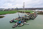 """Foto: VidiPhoto<br /> <br /> HETEREN – Met behulp van de drijvende bok Pionier worden donderdag grote en zware secties van de 88 meter lange, 18 meter brede en 16 meter hoge zandklasseerinstallatie Rotterdam 55 verwijderd. Het demonteren ligt volgens de Dekker Groep op schema. De """"55"""" is een enorme drijvende zandfabriek die de afgelopen jaren in de Plas van Wijck in de uiterwaarden langs de Rijn bij Heteren (Gelderland) 7,5 miljoen ton grof zand en grint heeft verwerkt voor de betonindustrie. De drijvende fabriek was 10 december voor het laatst actief en wordt nu gedemonteerd en binnenkort met een duwboot getransporteerd naar een opbouwlocatie langs de Waal. Het 'afbouwen' is nodig omdat het gevaarte anders niet onder de bruggen door kan. In ruil voor de grondwinningsvergunning richt de Dekker Groep het gebied, dat de naam Randwijkse Waarden heeft gekregen, in als natuur- en recreatieterrein. De werkzaamheden in de plas de komende jaren betreffen nu nog het opzuigen van fijn zand, geschikt voor wegen- en woningbouw en het opspuiten van eilandjes voor het natuur- en recreatiegebied."""