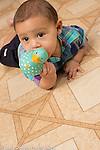 7 month old baby boy on stomach biting toy duck