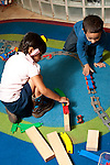 Education preschool 3-4 year olds boy and girl playing separately with train and wooden blocks and tracks