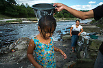 """November 07, 2014. """"Water it´s the real thing""""<br /> Edwin Salguero washes her daughter Nemia in Acelhuate river (Nejapa, El Salvador) because they don' t have drinking water at home. The river is contaminated. Edwin and his family have to walk near two hours to get the river. <br /> The people of Nejapa in El Salvador, have no drinking water because the Coca -Cola company overexploited the aquifer in the area, the most important source of water in this Central American country. This means that the population has to walk for hours to get water from wells and rivers. The problem is that these rivers and wells are contaminated by discharges that makes Coca- Cola and other factories that are installed in the area. The problem can increase: Coca Cola company has expansion plans, something that communities and NGOs want to stop. To make a liter of Coca Cola are needed 2,4 liters of water. ©Calamar2/ Pedro ARMESTRE"""